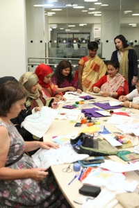 Women seated at a table sewing embroideries